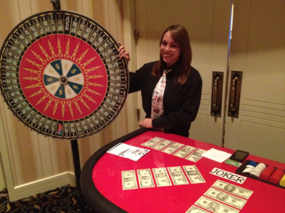 One of our professional and friendly casino dealers posing next to our beautiful money wheel.