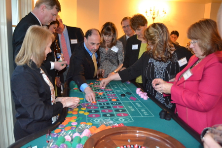 A crowded roulette table with players reaching to place their bets.