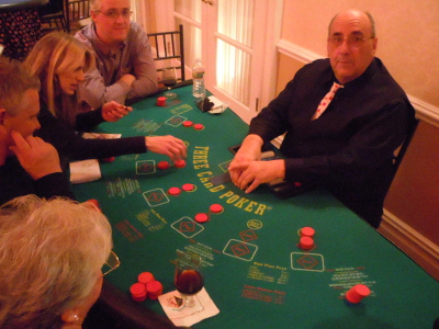 A professional Three Card dealer shuffling up the cards for the next hand.